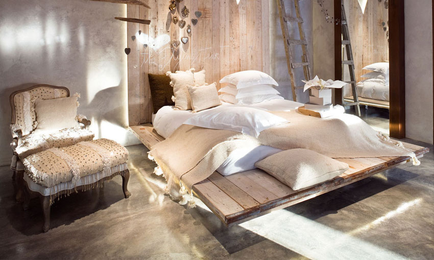 Concrete wall and floor are match with wood bed and snowy white & cream textiles