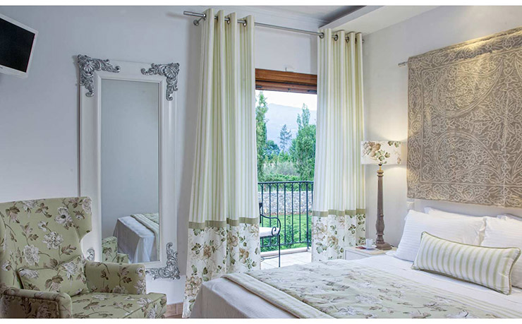 bedroom with lcurtains in light color in corfu villa