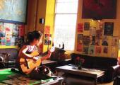 girl plays guitar on billiard table castle rock hostel